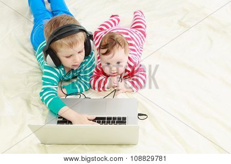 little brother and sister with laptop at home