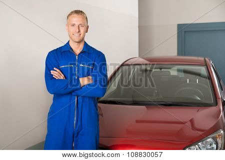 Mechanic Standing In Front Of Car With Folded Hands