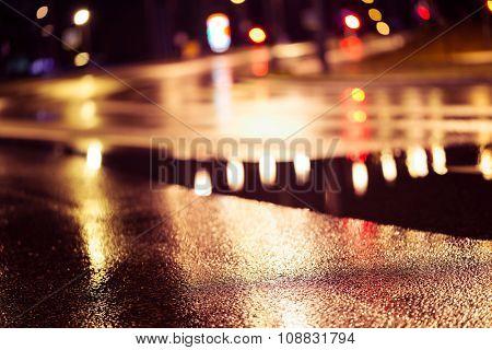 Abstract dark blurry urban background. Wet road.