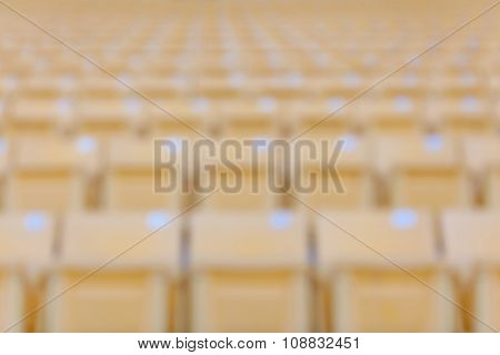 Abstract Blurred Background Of Yellow Seats At Football Stadium.