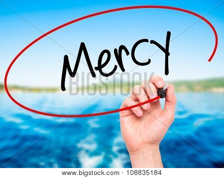 Man Hand writing Mercy with black marker on visual screen.