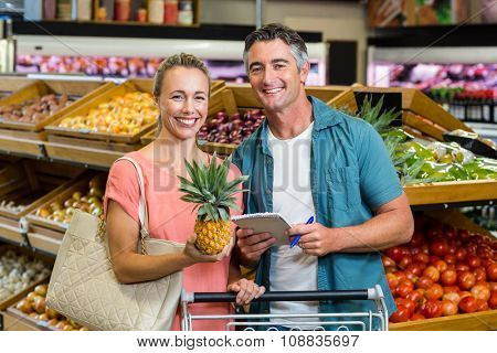 Smiling couple holding a pineapple and a grocery list at the supermarket