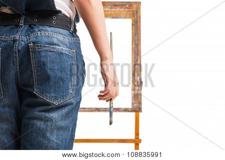 Young smiling woman painter with paintbrush standing at easel