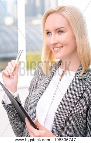 Confident businesswoman holding folder