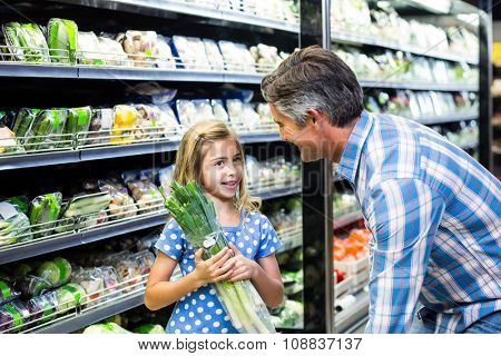 Father and daughter buying celery at the supermarket