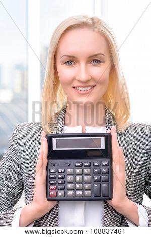 Pleasant businesswoman holding calculator