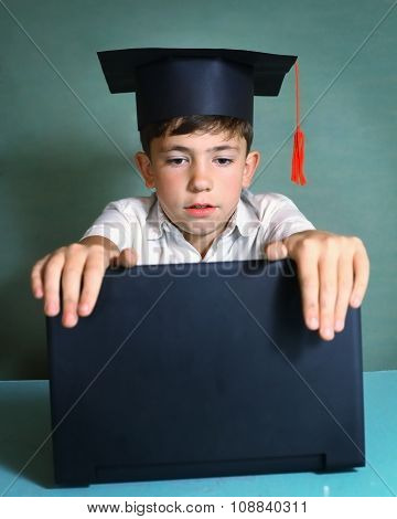 boy in graduation cap with  notebook