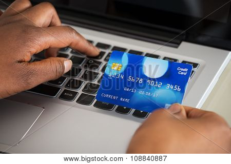 Person's Hand Using Debit Card While Shopping Online
