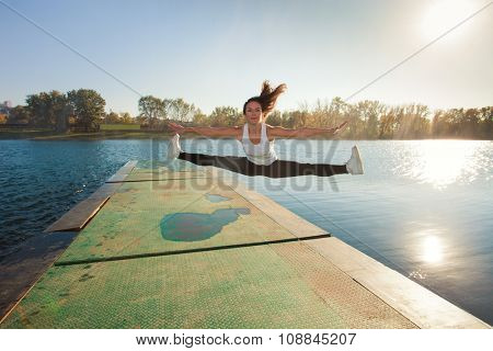 girl doing spaga in air by the lake,  sunny  autumn day, full body shot