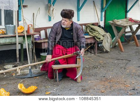 Ukrainian peasant getting ready to whet a scythe