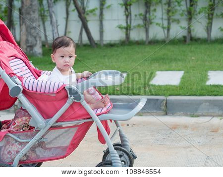 Asian Baby Girl Smiling And Look Joyful Sitting In Stroller.