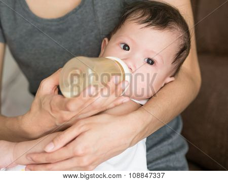 Asian Mother Feed Milk Her Baby In Bottle.