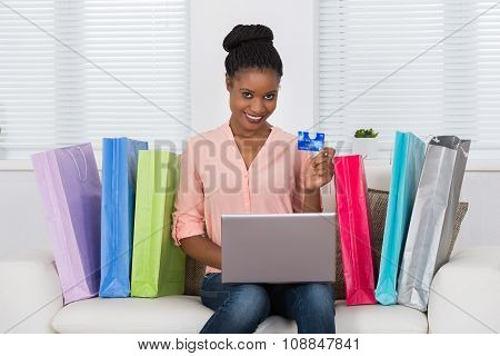 Woman Using Debit Card For Shopping On Laptop