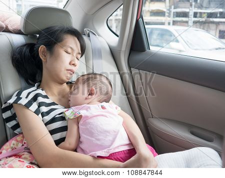 Asian Mother And Baby Sleeping In Car On Street.