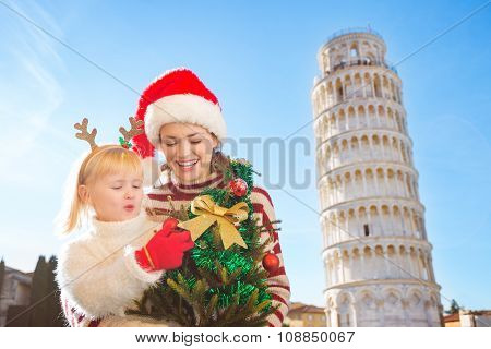 Happy Mother And Daughter Holding Christmas Tree. Pisa, Italy