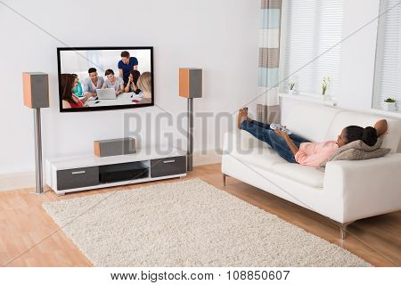 Woman Watching Television While Lying On Sofa