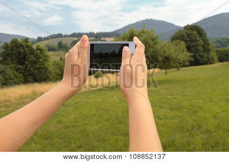 Hands Of Young Woman With Smartphone That Take a Photo In Nature