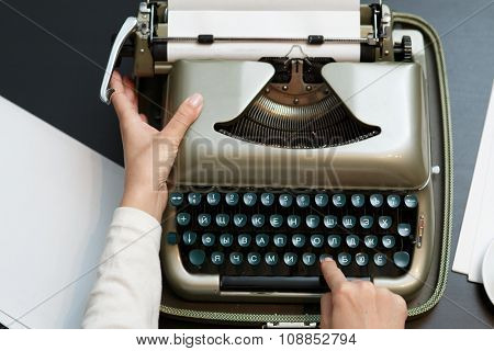 closeup of woman typing with old typewriter top view
