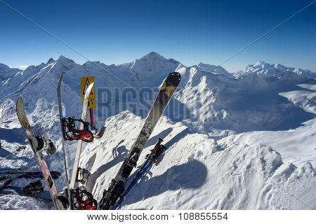 Skis And Snowboards Standing Upright In Snow