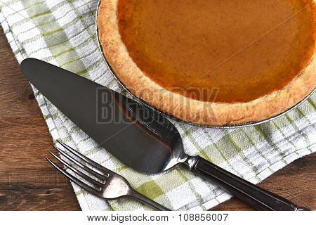 High angle view of a pumpkin pie, server and fork. The dessert is part of a typical Thanksgiving Day Feast.