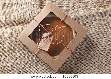 Fresh pumpkin pie in a bakery box tied with string and a blank tag. High angle view on a burlap surface.