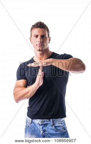 Young man gesturing time out sign with his hands
