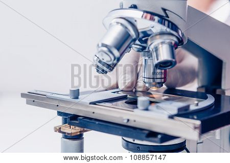 Scientist hands with microscope
