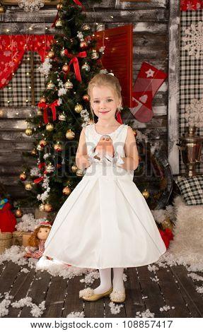 Cute Young beautiful girl wears Christmas dress. She has a littl