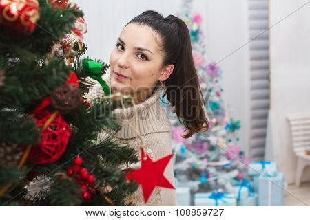 Girl peeping from behind Christmas tree
