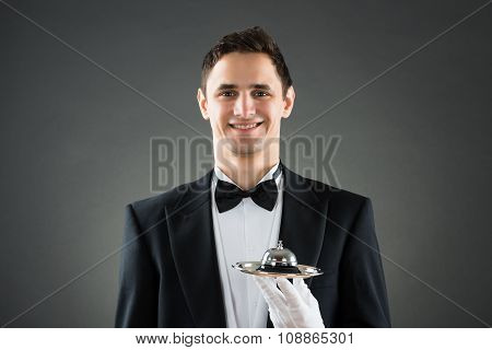 Happy Waiter Holding Service Bell In Plate