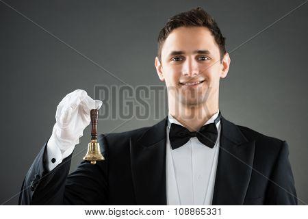 Portrait Of Smiling Waiter Holding Ring Bell