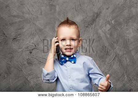 Portrait Of A Cute Little Boy In Blue Shirt And Bow Tie With Mobile Phone Against Gray Textural Back