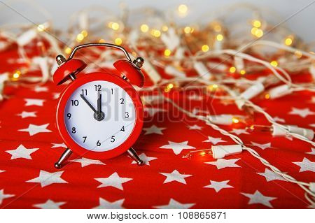 Red Alarm Clock With Lights Bokeh On A Red Fabric Background With Stars