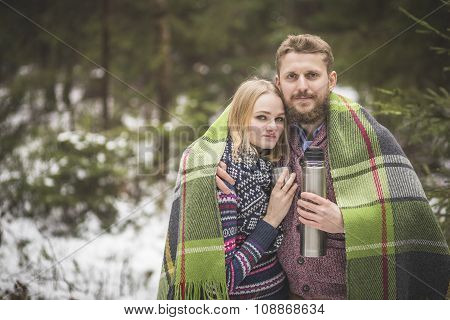 Young couple in a warm blanket with thermos flask