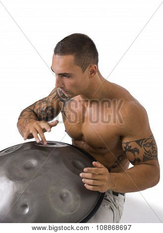 Exotic Male Drummer Drumming with Hands on Steel Pan Drums, While Seated in Studio Isolated on White Background