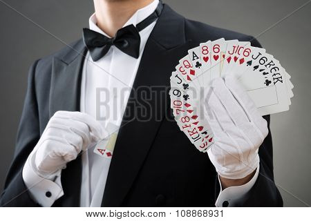 Magician Showing Fanned Out Cards Against Gray Background