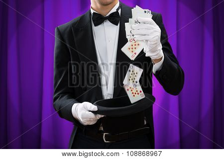 Midsection Of Magician Performing Trick With Cards And Hat
