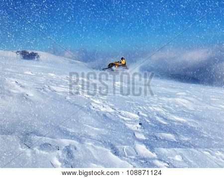 People driving snowmobile in winter mountain. Winter snowfall