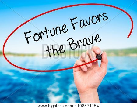 Man Hand writing Fortune Favors the Brave with black marker on visual screen