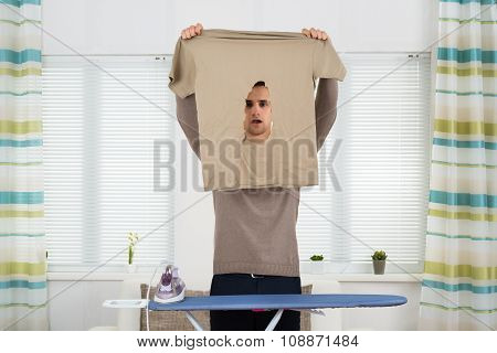 Shocked Man Looking At Iron Burnt Tshirt