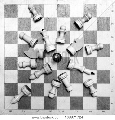 black white chess board and pieces scattered on the board on the black white background