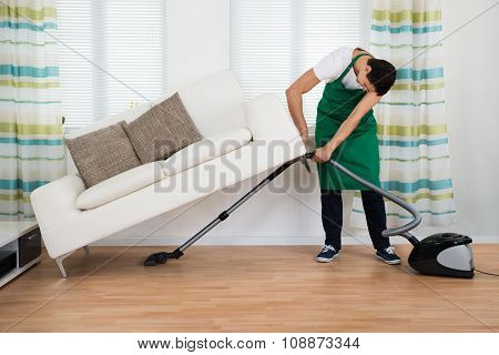 Man Lifting Couch While Cleaning Floor With Vacuum Cleaner
