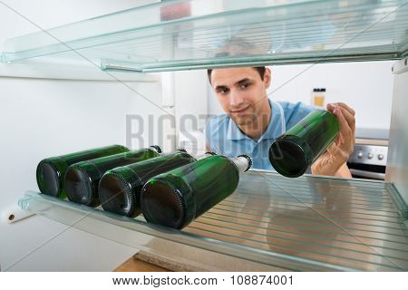 Smiling Man Removing Beer Bottle From Refrigerator