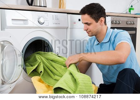 Man Loading Towels In Washing Machine