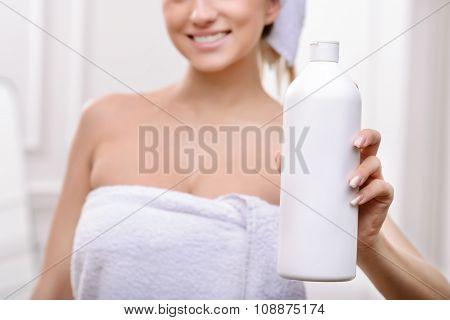 Positive girl holding bottle of shampoo