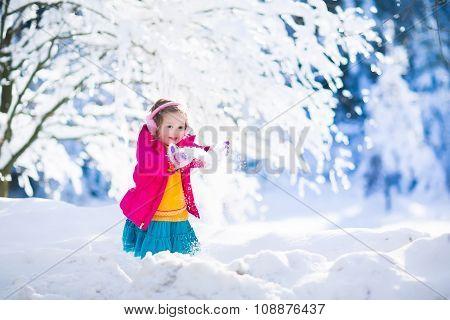Child Having Fun In Winter Snowy Park