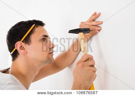 Man Hammering Nail On White Wall