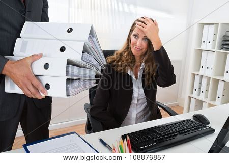 Businessman Giving Pile Of Folders To Female Assistant