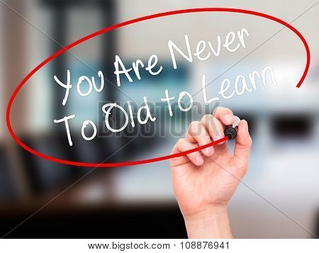 Man Hand writing You Are Never Too Old to Learn with black marker on visual screen.