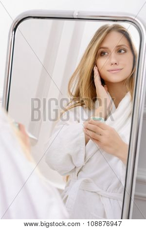 Pleasant woman using cream for body